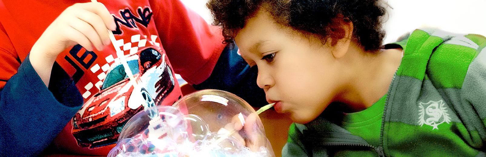Junge beim Experimentieren mit Seifenblasen